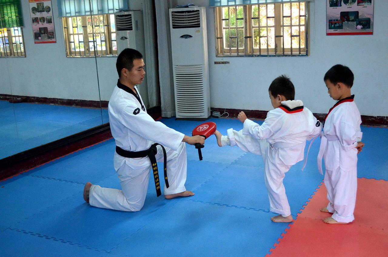 Imagem mostra duas crianças praticando karatê junto a um adulto.