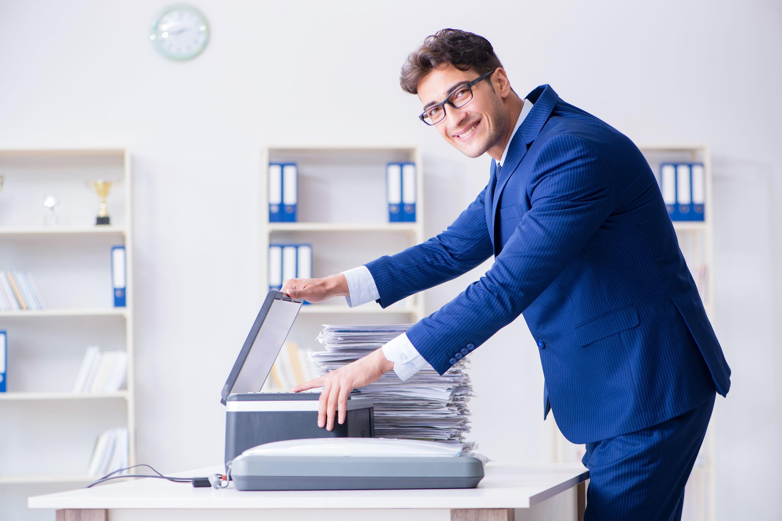 Na imagem está um homem de terno dentro de um escritório utilizando um scanner.