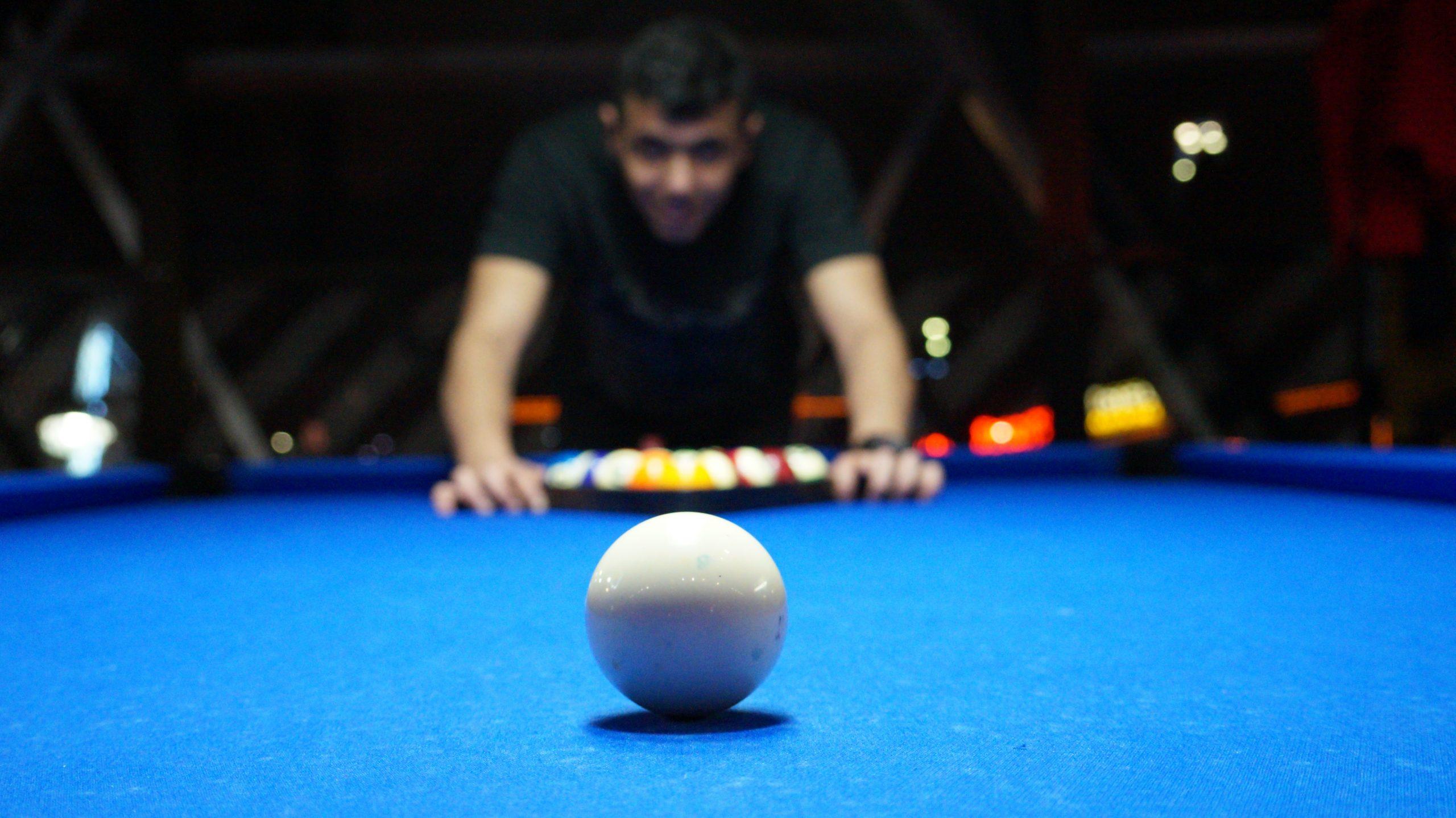 Imagem mostra uma mesa de bilhar azul, focada na bola branca. Ao fundo, desfocada, uma pessoa ajeita as demais bolas coloridas.