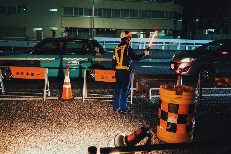 homem à noite colocando cones na rua.