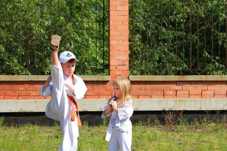 Imagem mostra duas crianças treinando karatê lado a lado.