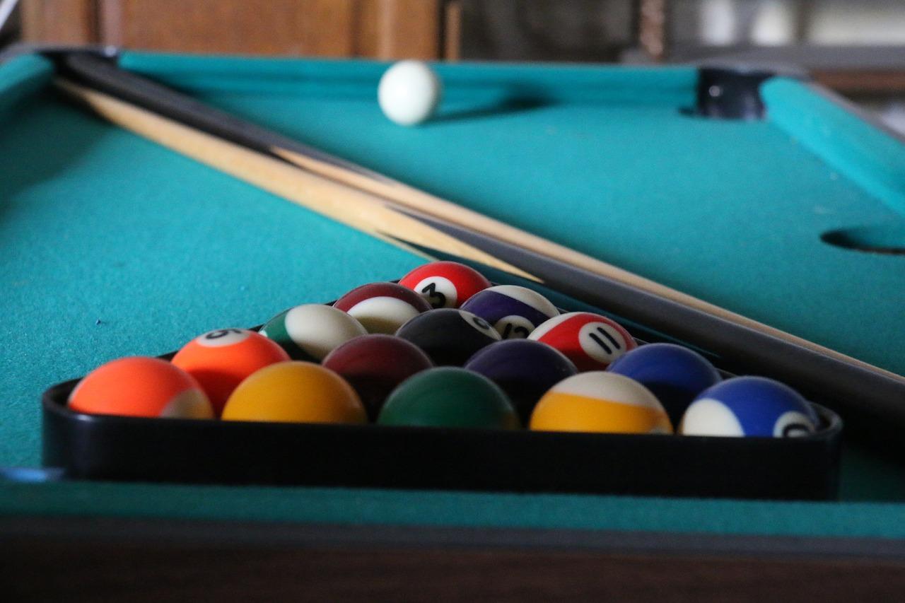 Uma mesa de sinuca com bolas de bilhar dentro de um triângulo de plástico, um taco de sinuca e uma bola branca.