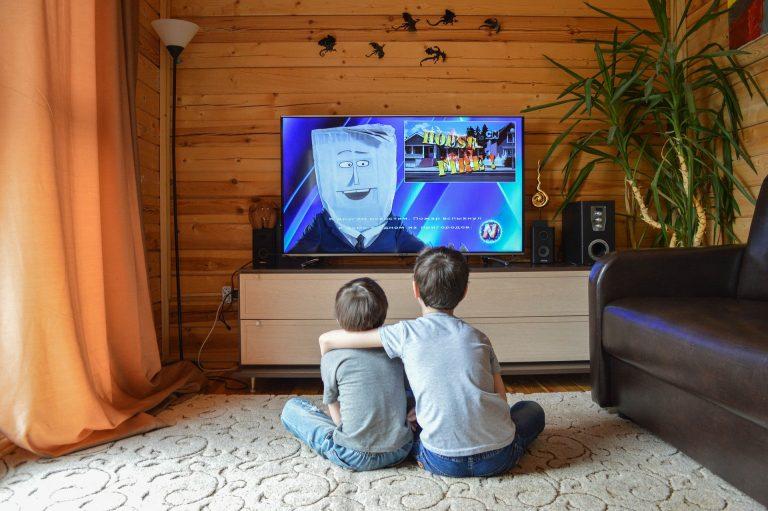 Imagem mostra duas crianças assistindo a uma televisão com sistema de som completo.