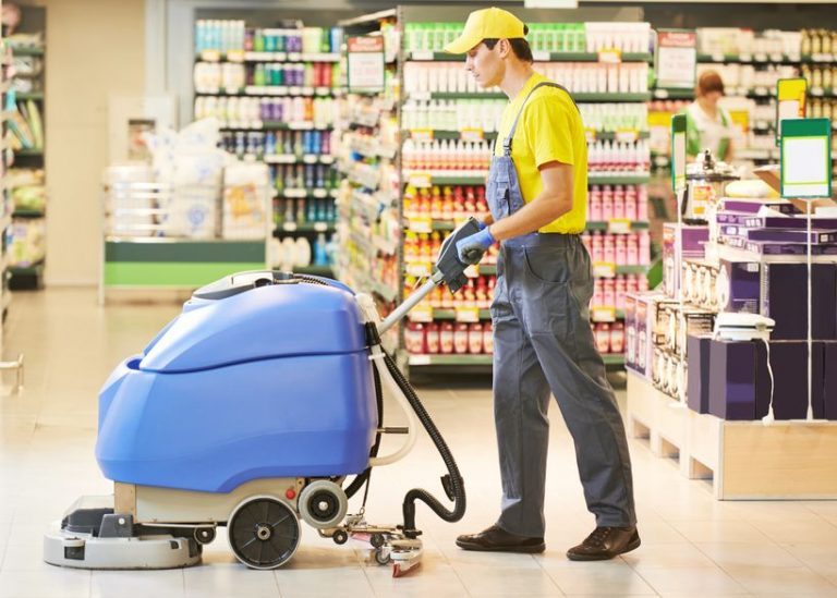 Homem usando uma varredeira para limpar o chão do supermercado.