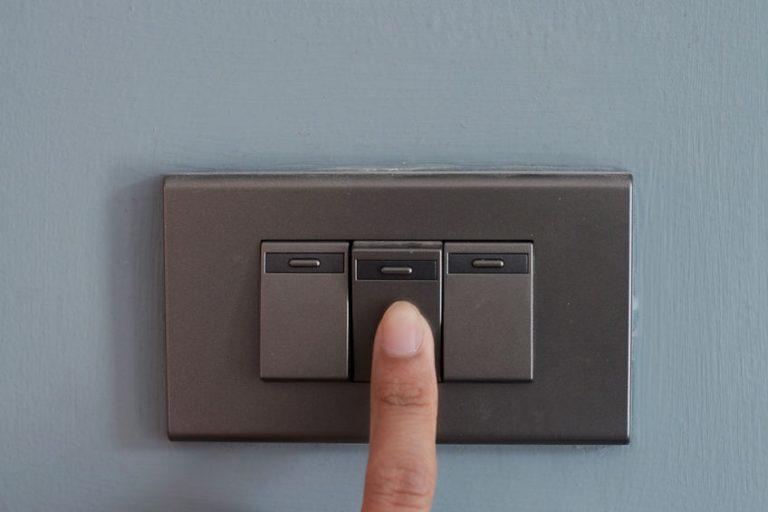 Dedo acionando o interruptor de luz.