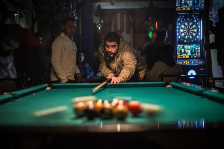 """Imagem mostra um rapaz, num bar, """"estourando"""" as bolas, iniciando a partida de sinuca."""
