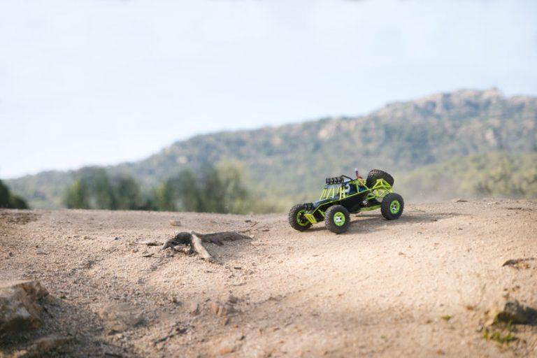 Foto de um carrinho de controle remoto andando sobre areia, bem próximo à água.