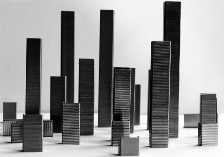 grampos de grampeador empilhados em diferentes alturas e distâncias num fundo branco.