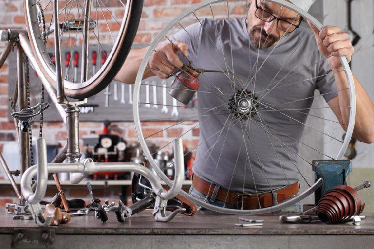 Imagem mostra um homem trabalhando na remoção de ferrugem de uma bicicleta.
