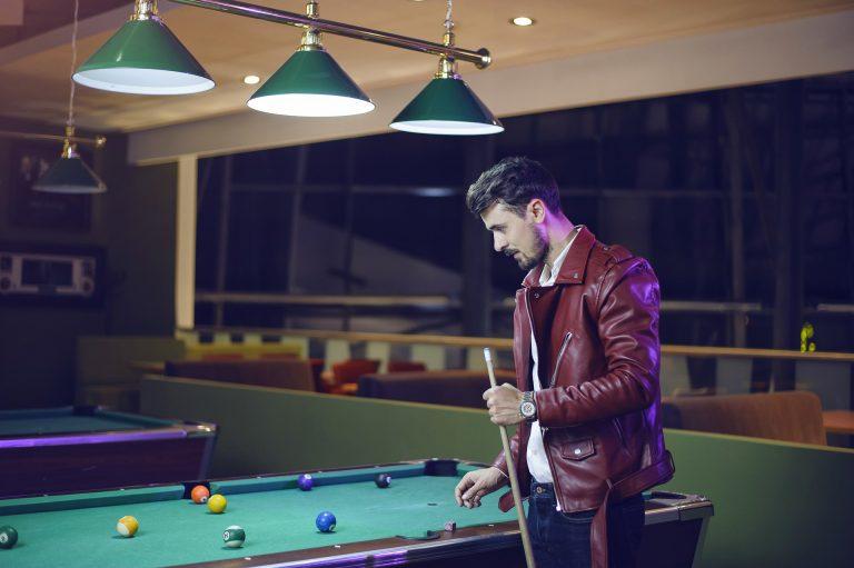 Um homem com jaqueta de couro com um taco na mão olhando para uma mesa de sinuca.