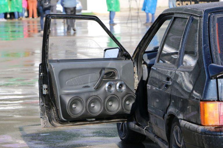 Imagem mostra um carro com diversos alto-falantes na porta.