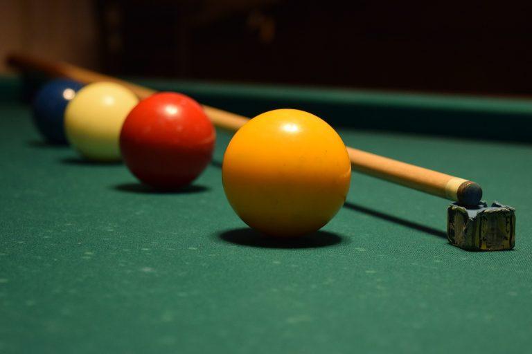 Imagem mostra uma fileira de bolas de sinuca coloridas, escoradas num taco de bilhar.