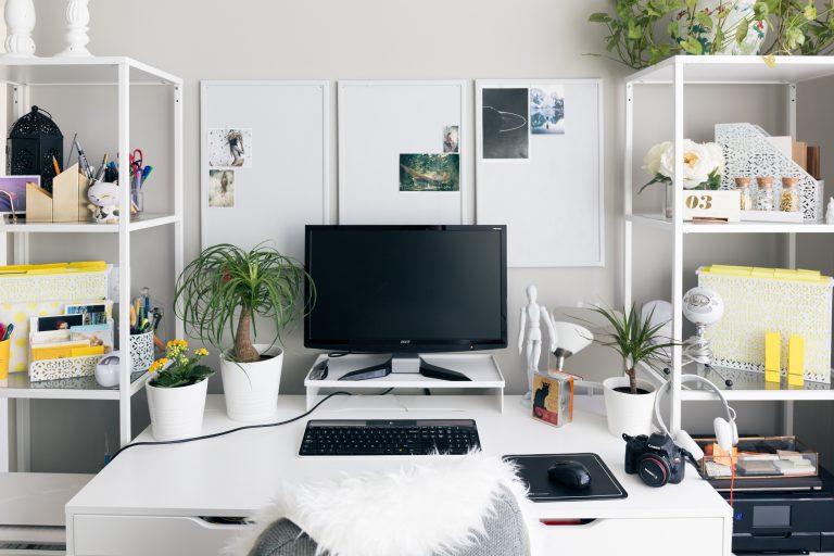 Na foto um escritório com móveis brancos e duas prateleiras nas laterais.
