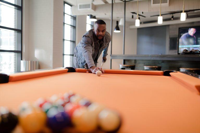 Imagem mostra um rapaz na sua casa, sozinho, dando início à um jogo de sinuca.