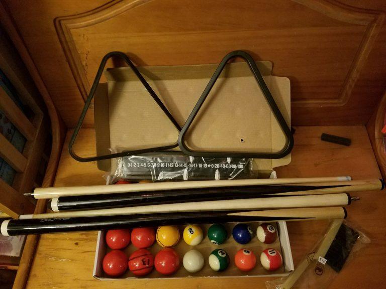 Um kit com 14 bolas de bilhar, 2 tacos de sinuca rosqueáveis e 2 triângulos em cima de uma mesa de madeira.