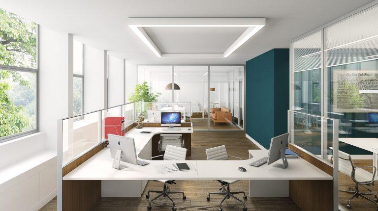 Na foto um escritório com diversas mesas de trabalho.