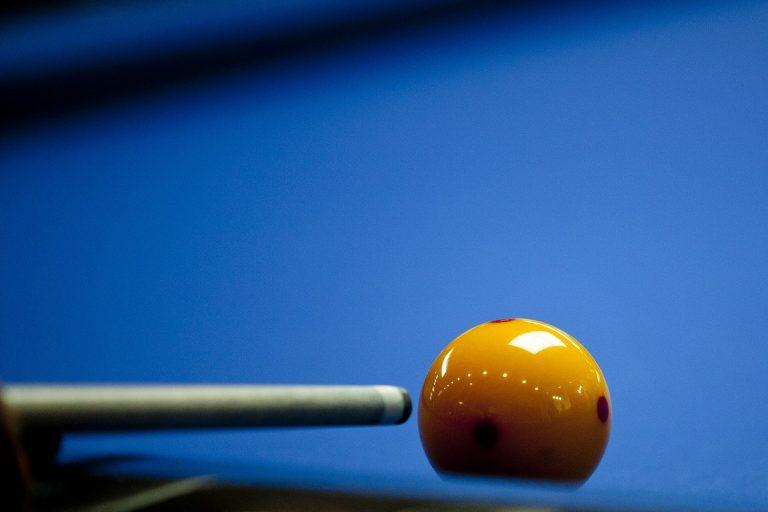 Imagem mostra um close de um taco de bilhar se aproximando de uma bola amarela bem brilhante.