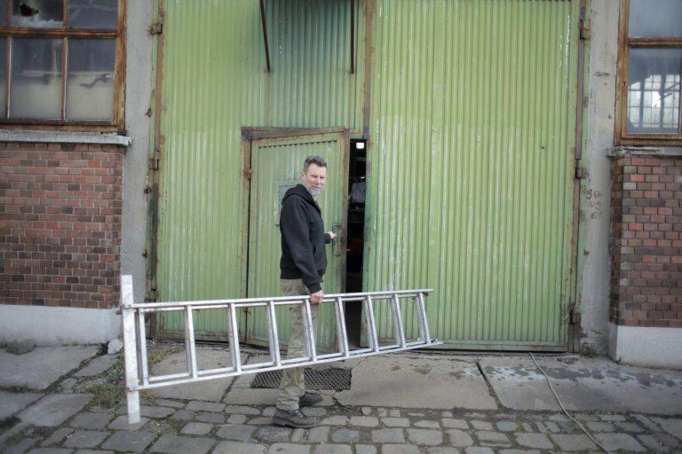 Imagem mostra um homem carregando uma escada de sete degraus.