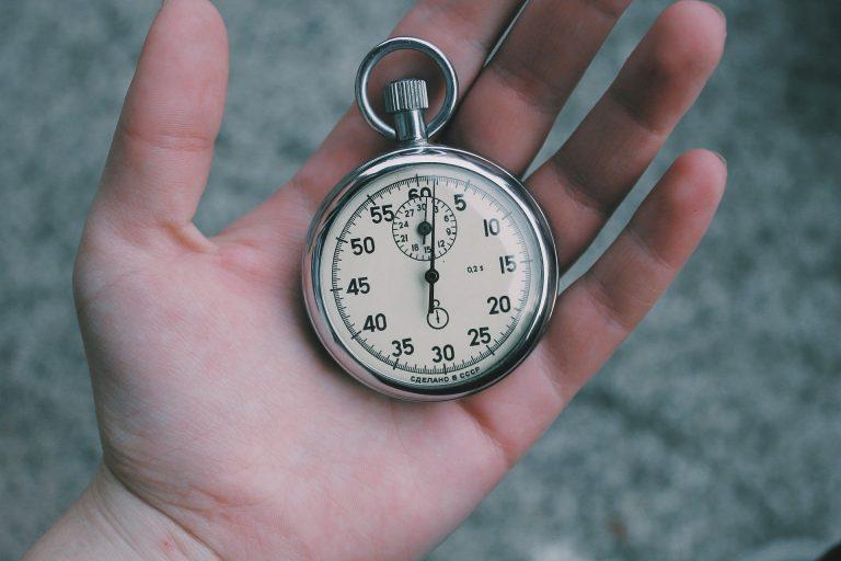 cronometro analógico, em funcionamento, sendo segurado por uma mão.