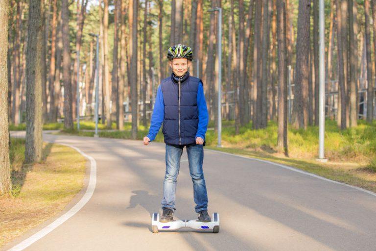 Imagem mostra uma criança andando de skate elétrico em uma estrada.