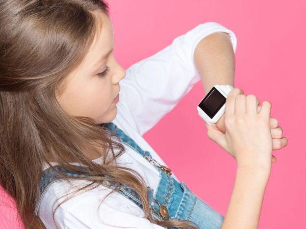 Menina olhando para relógio de pulso.