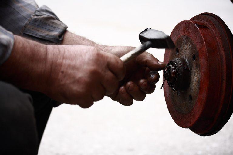 Imagem mostra um mecânico usando martelo de borracha em uma roda.