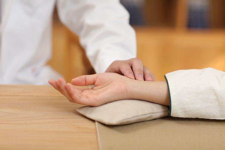 Médico avaliando pulso de paciente.