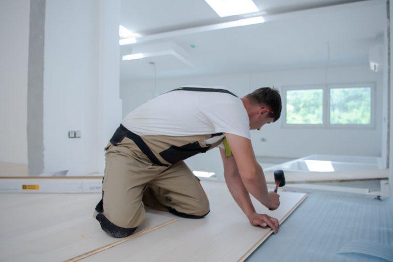 Imagem mostra um homem usando martelo de borracha na instalação de pisos.