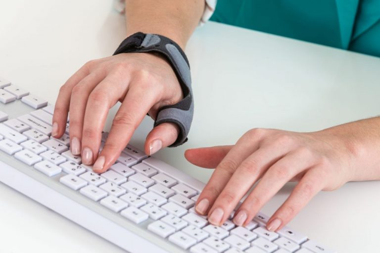 Mão com munhequeira digitando no teclado do computador.