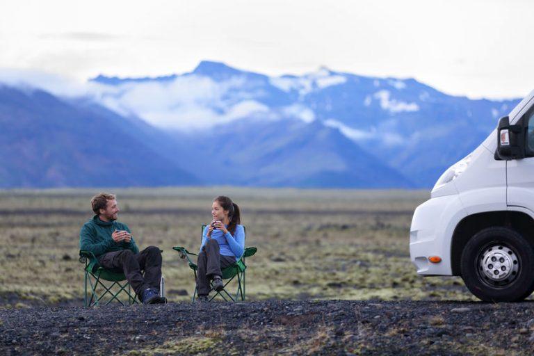 Imagem mostra duas pessoas em cadeiras de acampamento ao lado de um grande veículo.