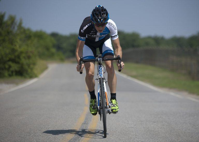 Imagem de um homem com capacete e óculos de ciclismo pedalando em uma estrada vazia
