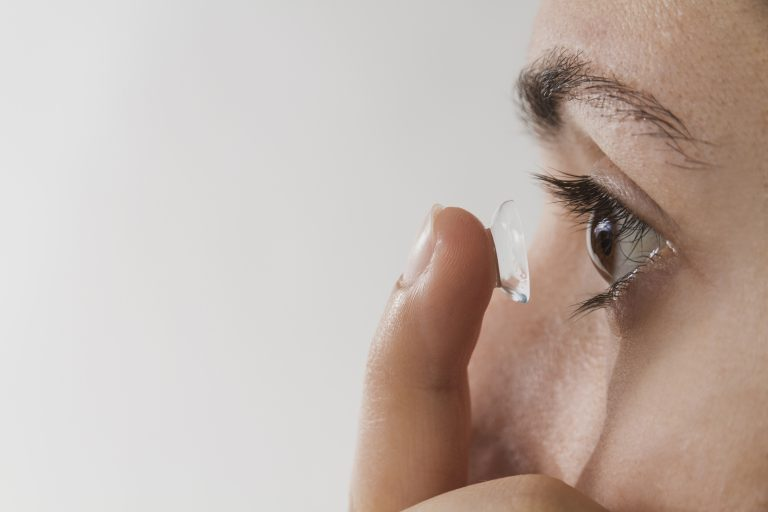 Imagem de uma mulher colocando lente de contato em um de seus olhos