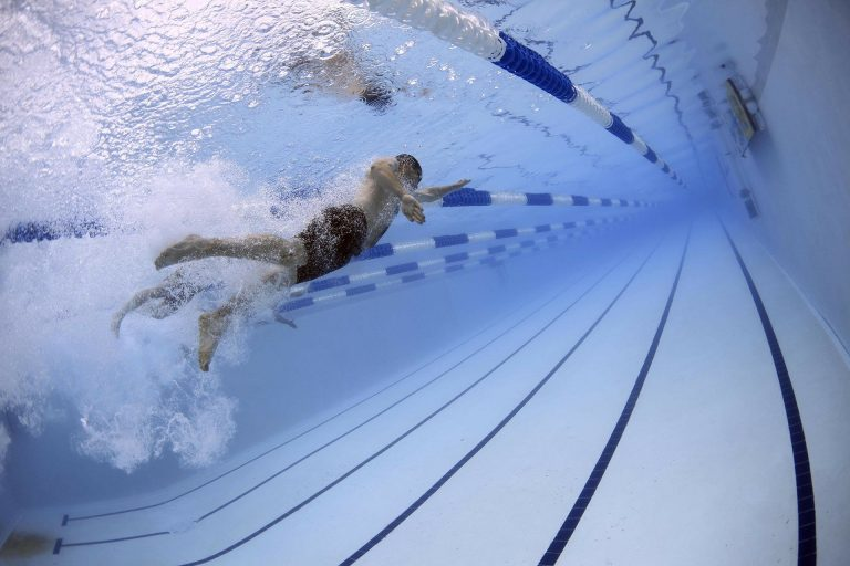 foto de um nadador em competição, com outros próximos.