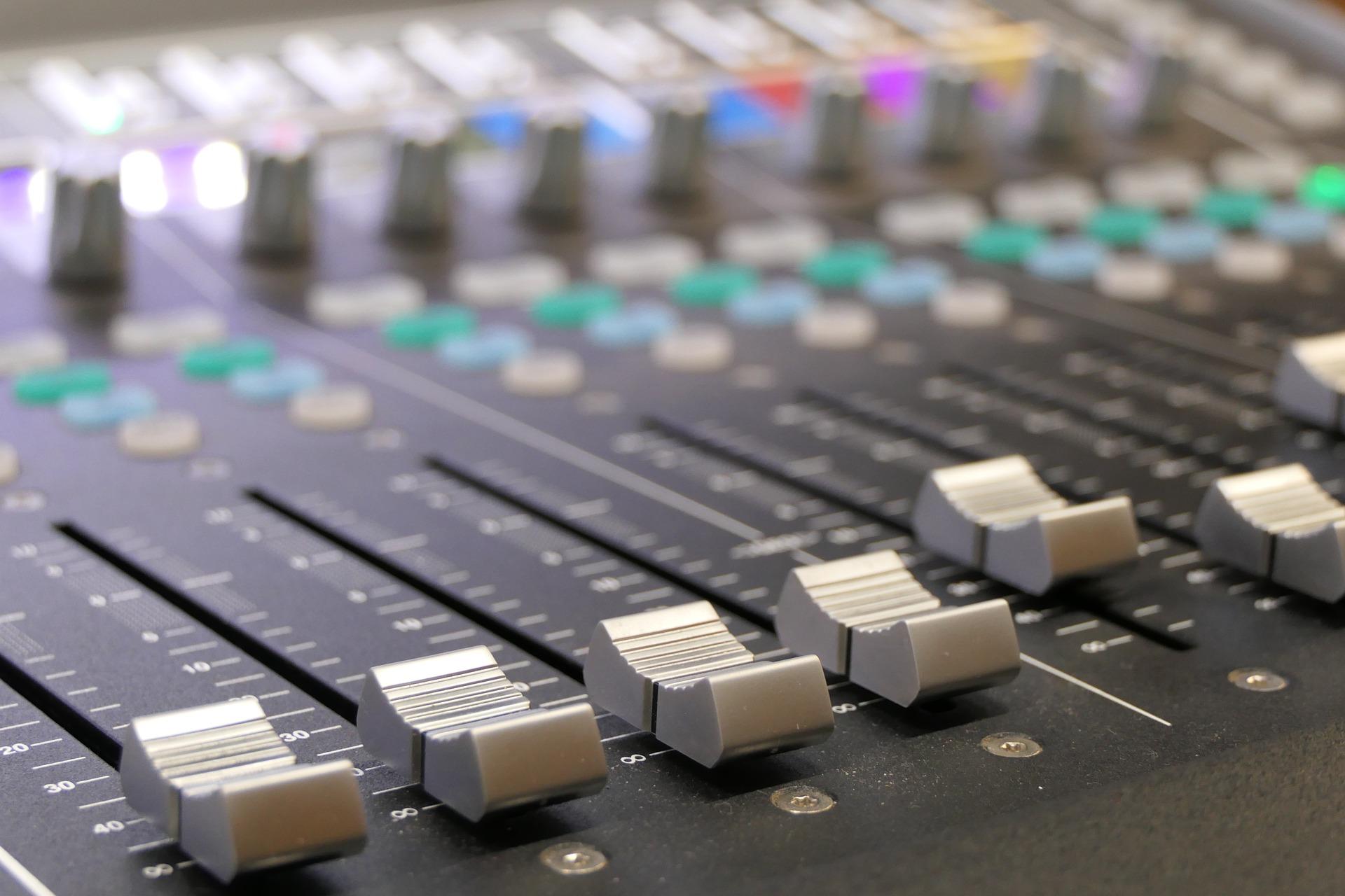 Imagem mostra uma mesa de som em detalhe.