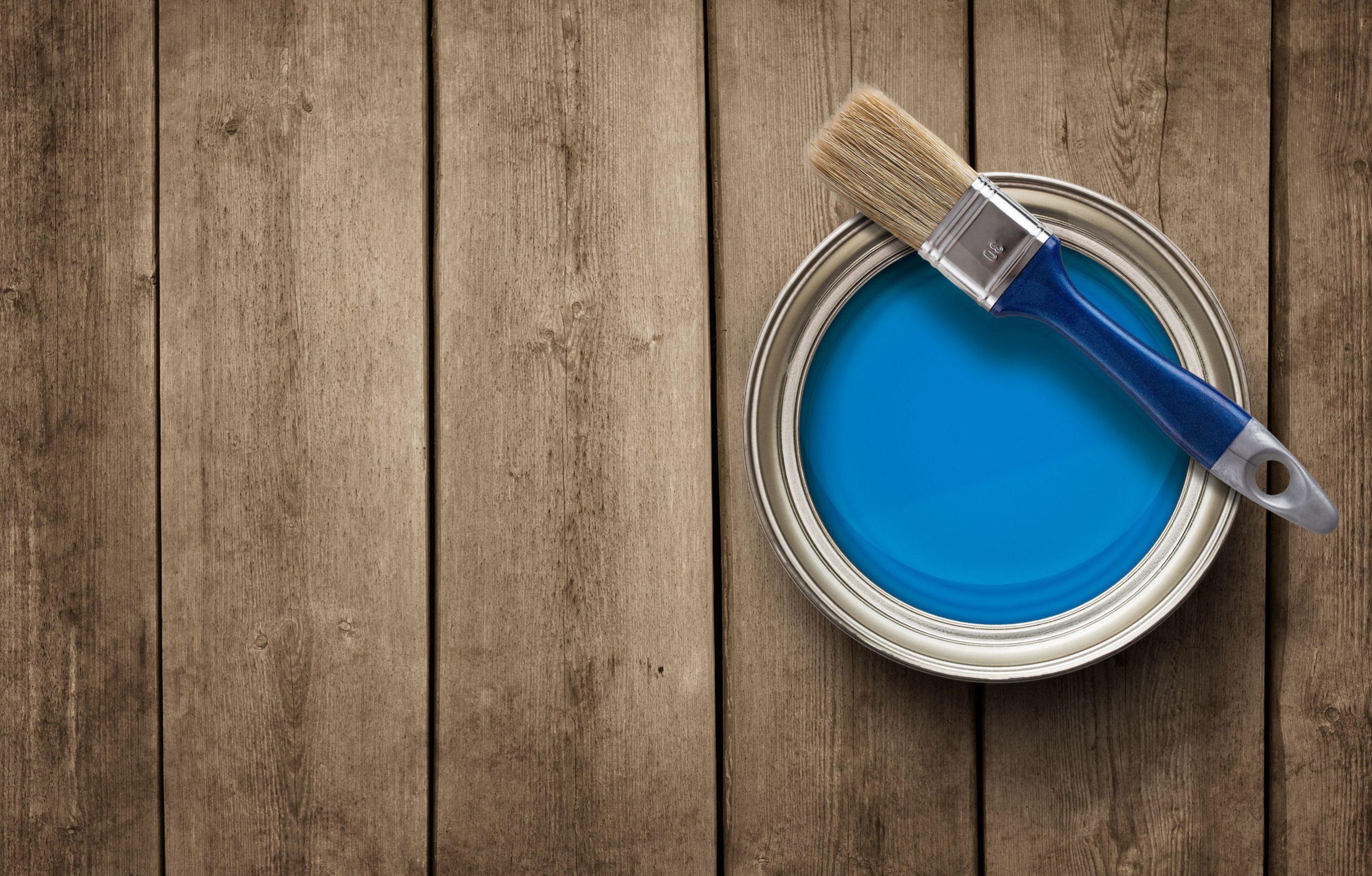 Galão de tinta, com pincel, sobre piso.
