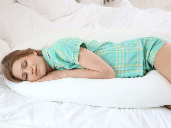 Beautiful pregnant woman sleeping with body pillow