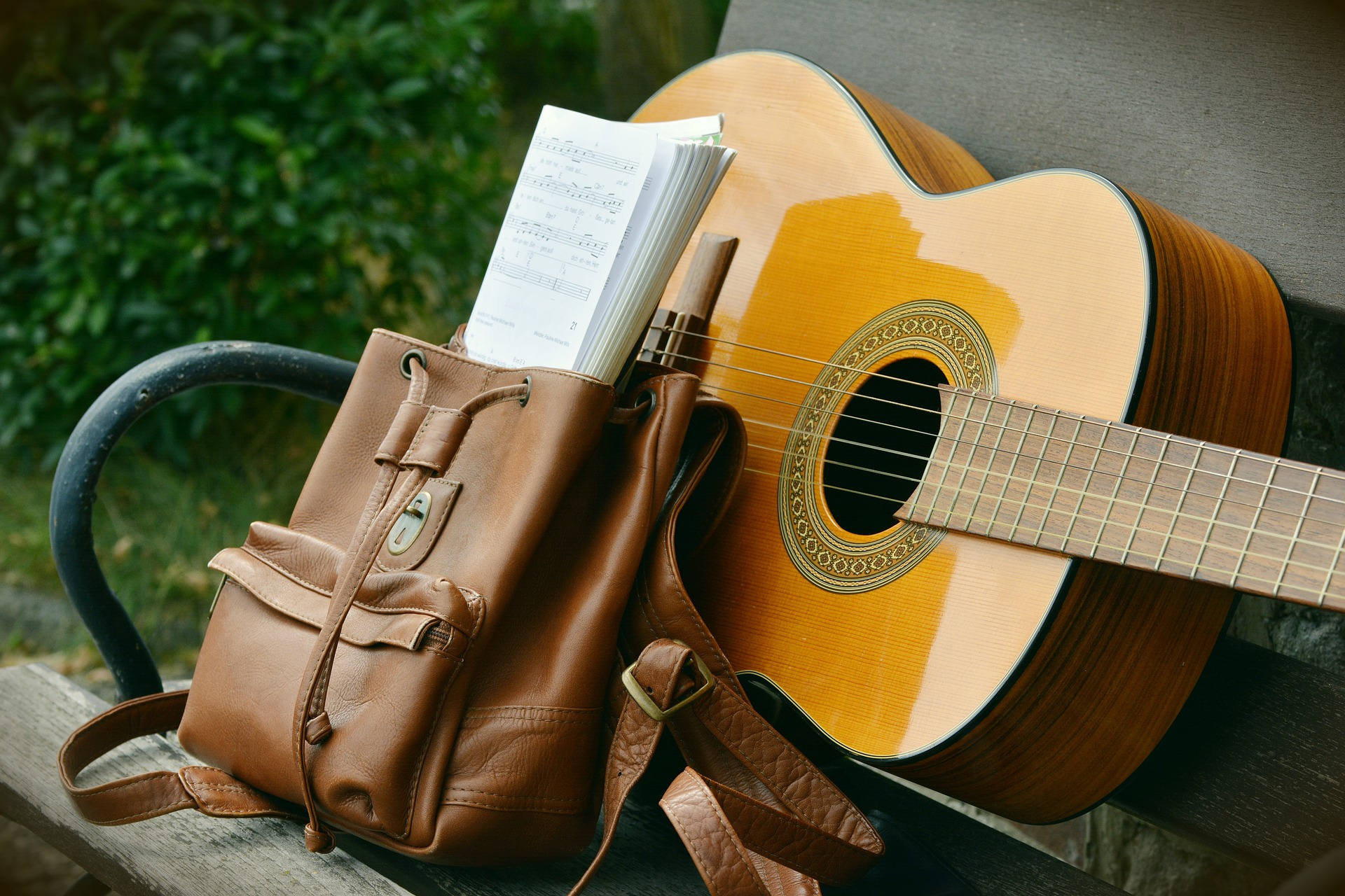 Image shows a guitar next to a bag with a score.