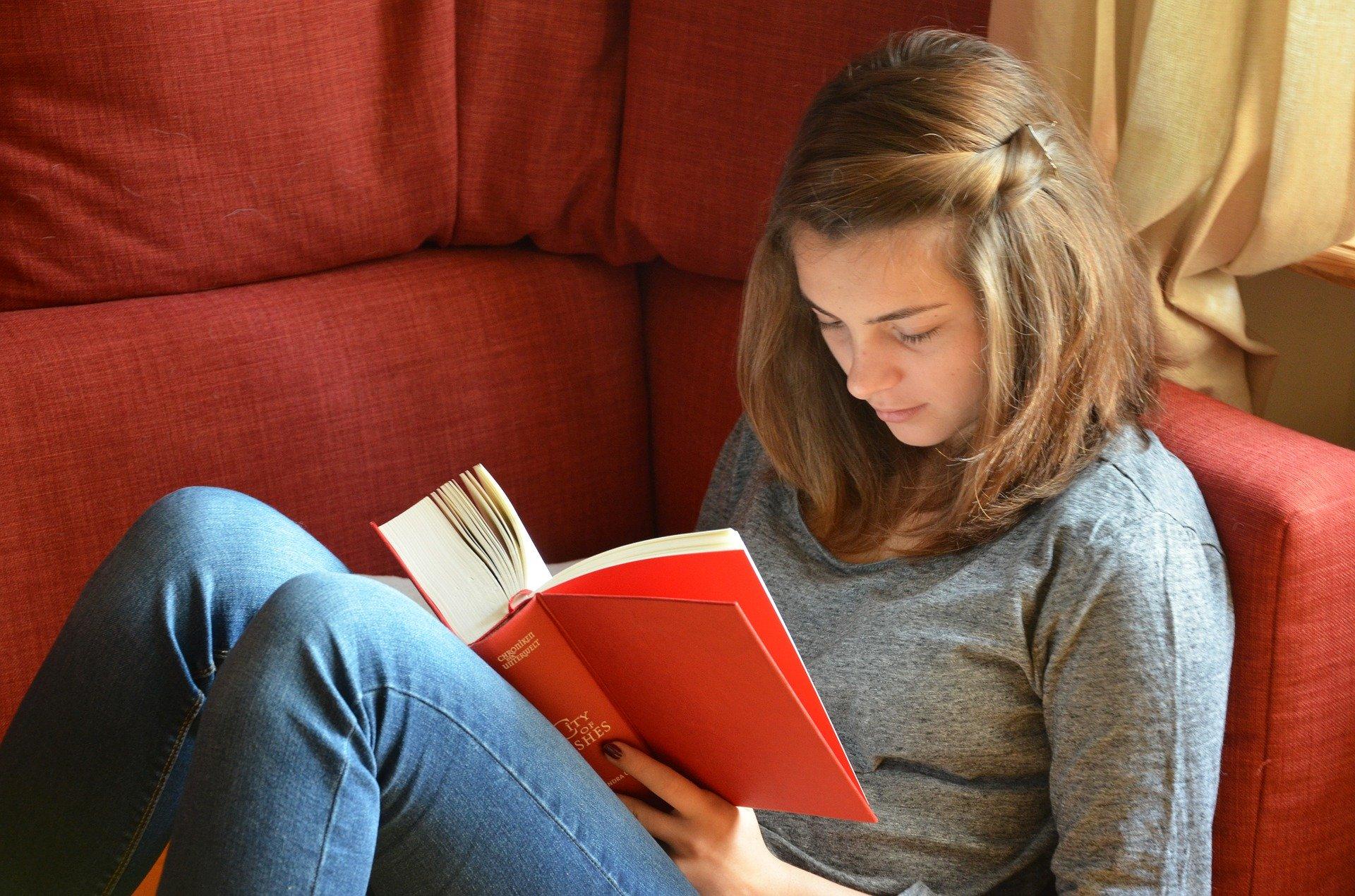 Imagem mostra uma jovem mulher lendo um livro.