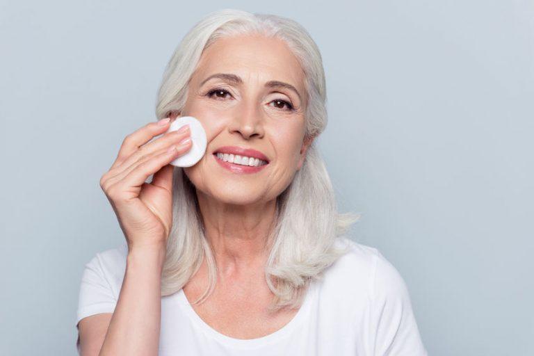 Mulher idosa passando algodão com produto na pele do rosto.