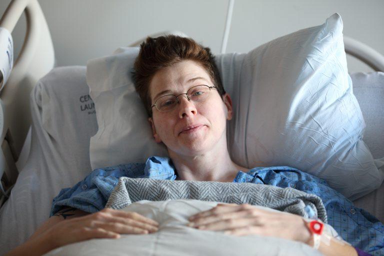 Mulher deitada em cama hospitalar.