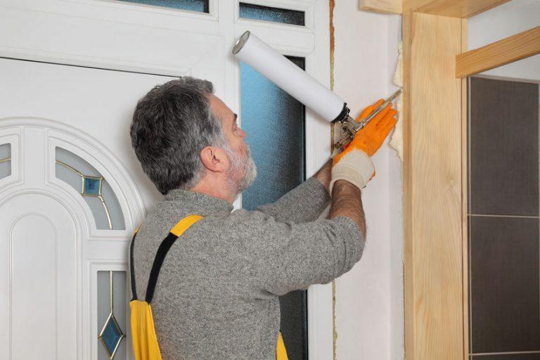 Imagem mostra um homem usando espuma expansiva na colocação de uma porta.