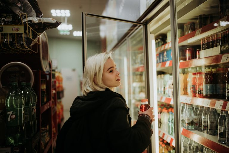 Mulher pegando bebida em geladeira de comércio.