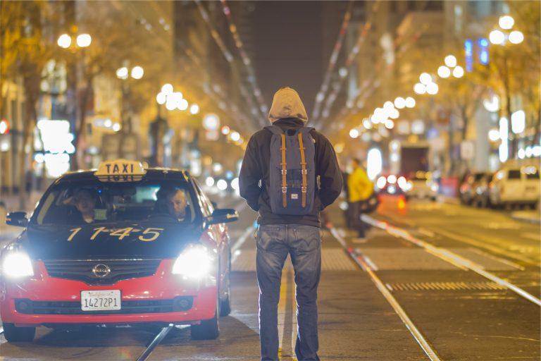 Imagem mostra um mochileiro andando à noite em uma rua ao lado de um táxi com farol aceso.