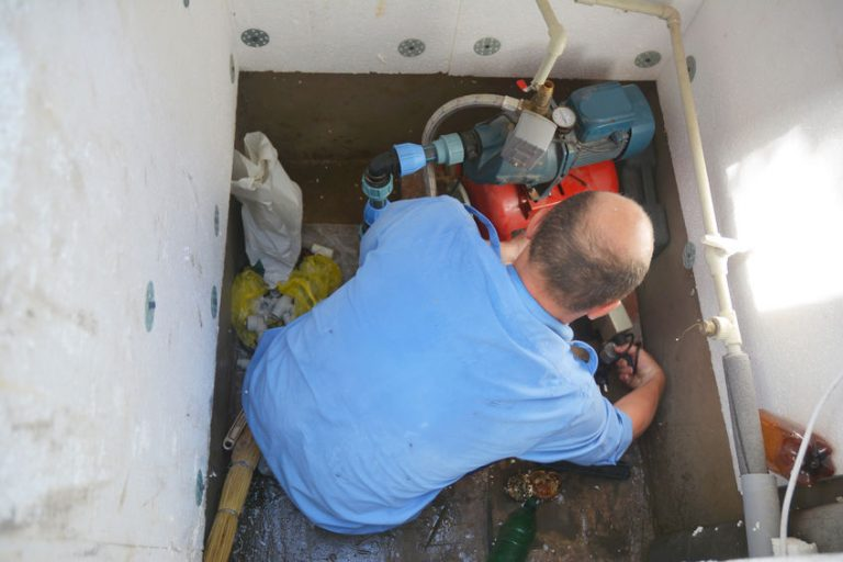Imagem mostra um homem mexendo em uma motobomba em uma caixa d'água.