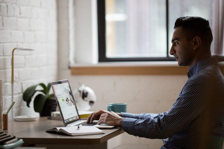 Imagem mostra um homem programando em um notebook.