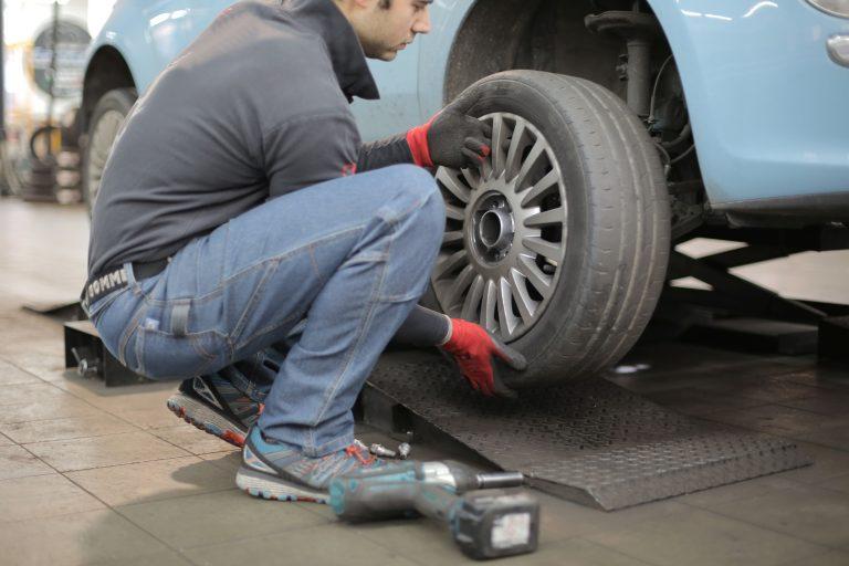 Imagem mostra um homem fazendo a troca de um pneu de um carro.