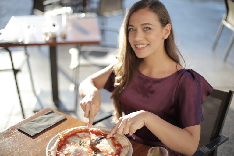 Imagem de uma mulher almoçando.
