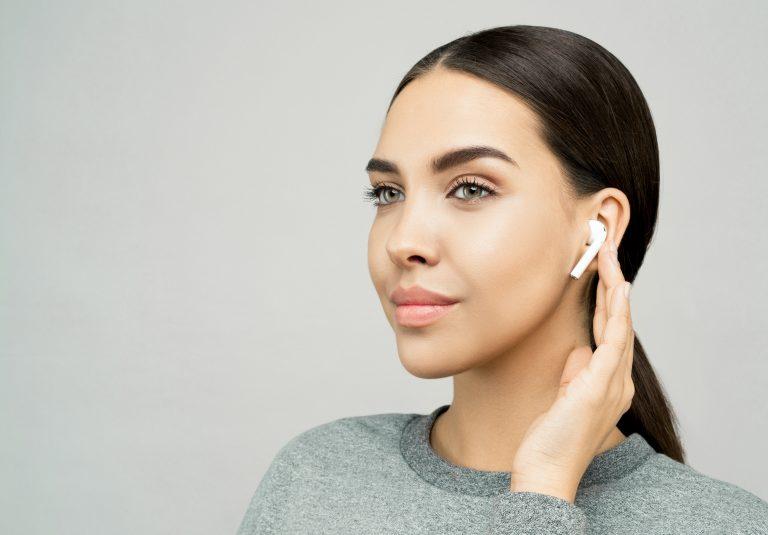 Imagem mostra uma mulher usando fone de ouvido intra auricular sem fio.