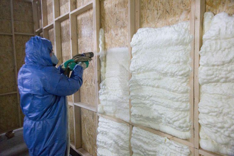 Imagem mostra um homem preenchendo uma parede com espuma expansiva.