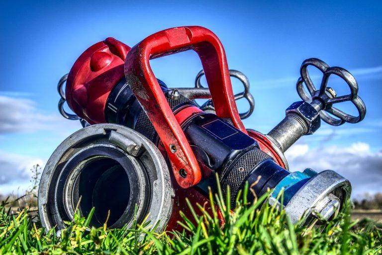 Imagem mostra uma motobomba sobre um gramado.